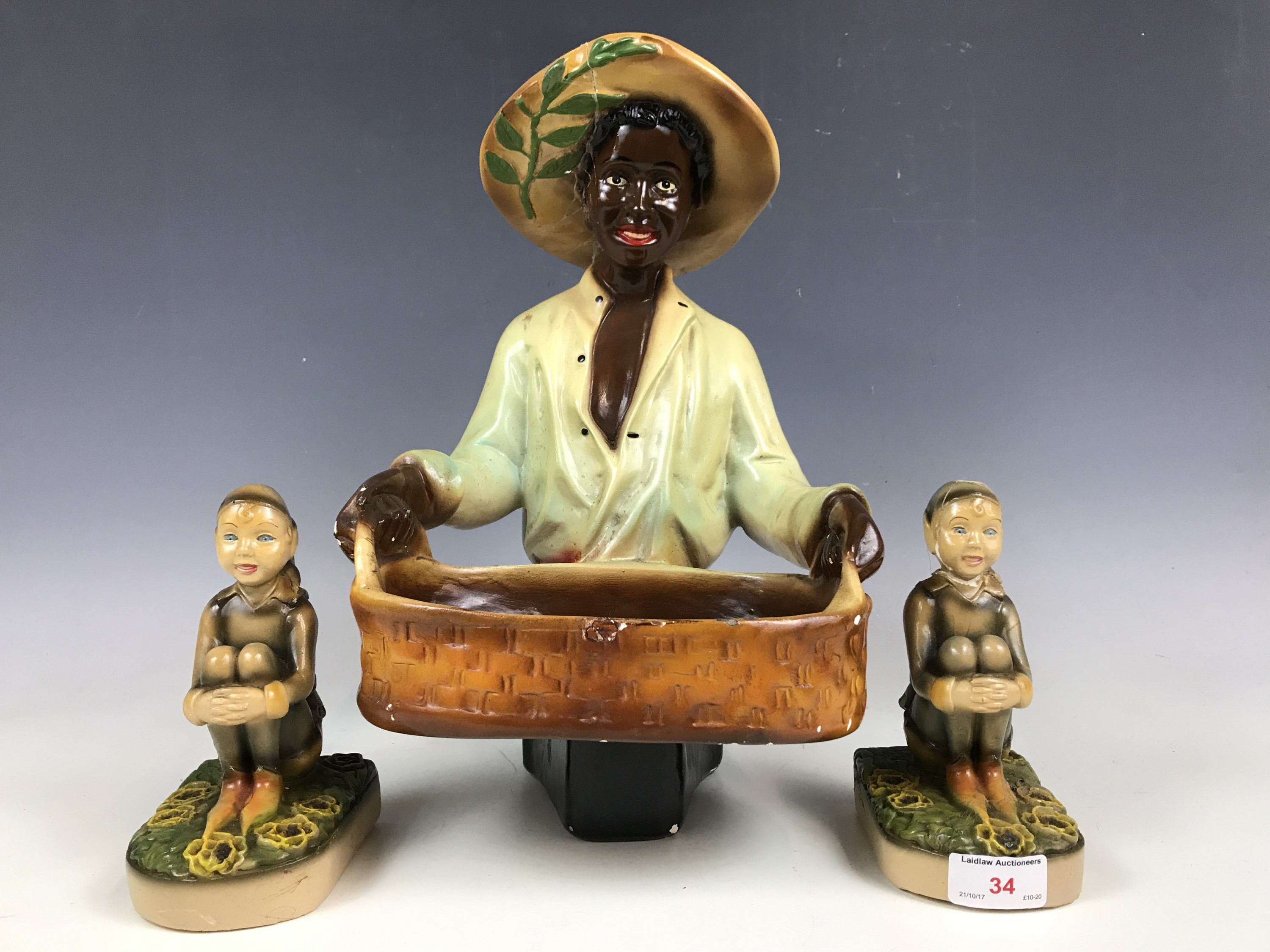 Lot 34 - A 1940's kitsch plaster figure together with two similar bookends (a/f)