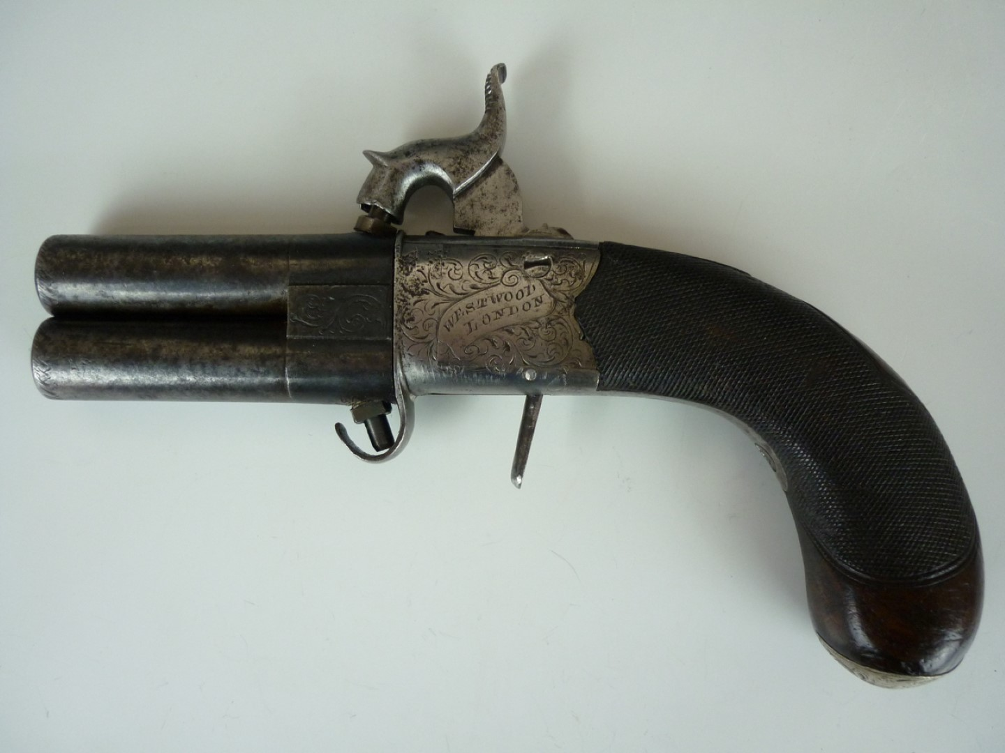 Lot 117 - A late Georgian pocket percussion double-barrelled turn-over pistol by Joseph Westwood, having 2 1/