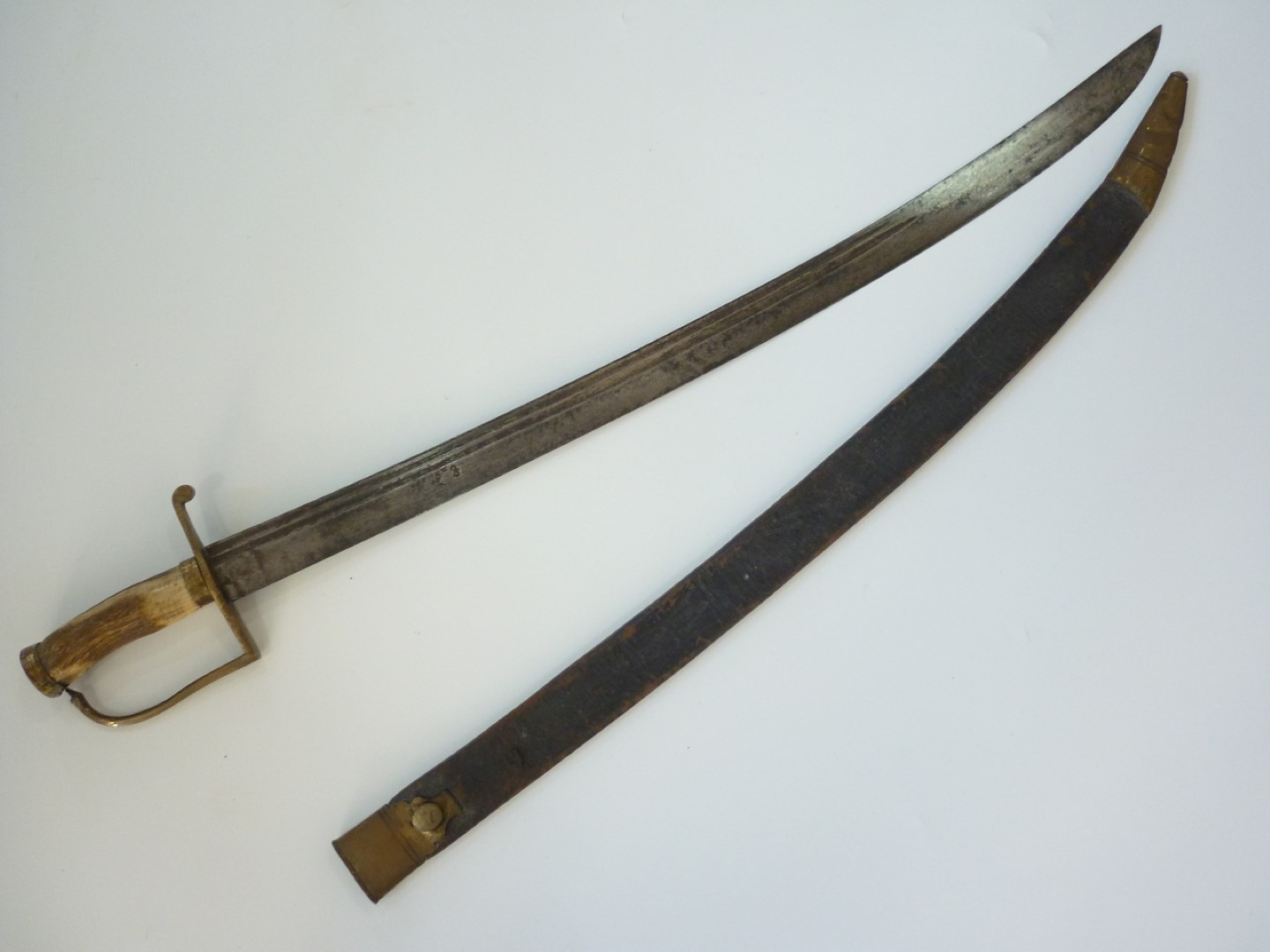 Lot 94 - A George III Naval cutlass, having brass stirrup hilt with antler grip, double fullered curved