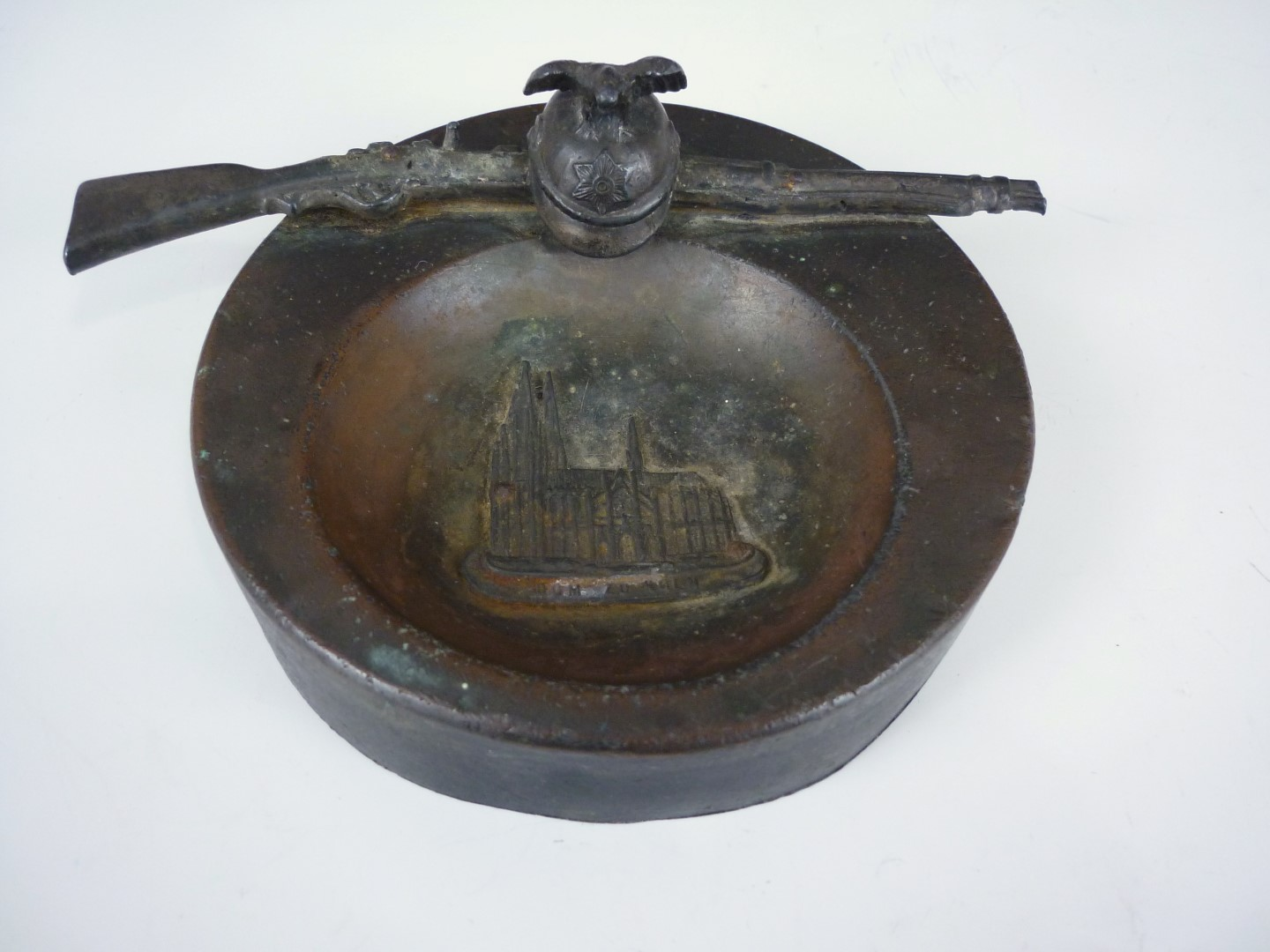 Lot 72 - An early 20th Century German bronzed spelter dish modelled as a Garde du Corps helmet and rifle,