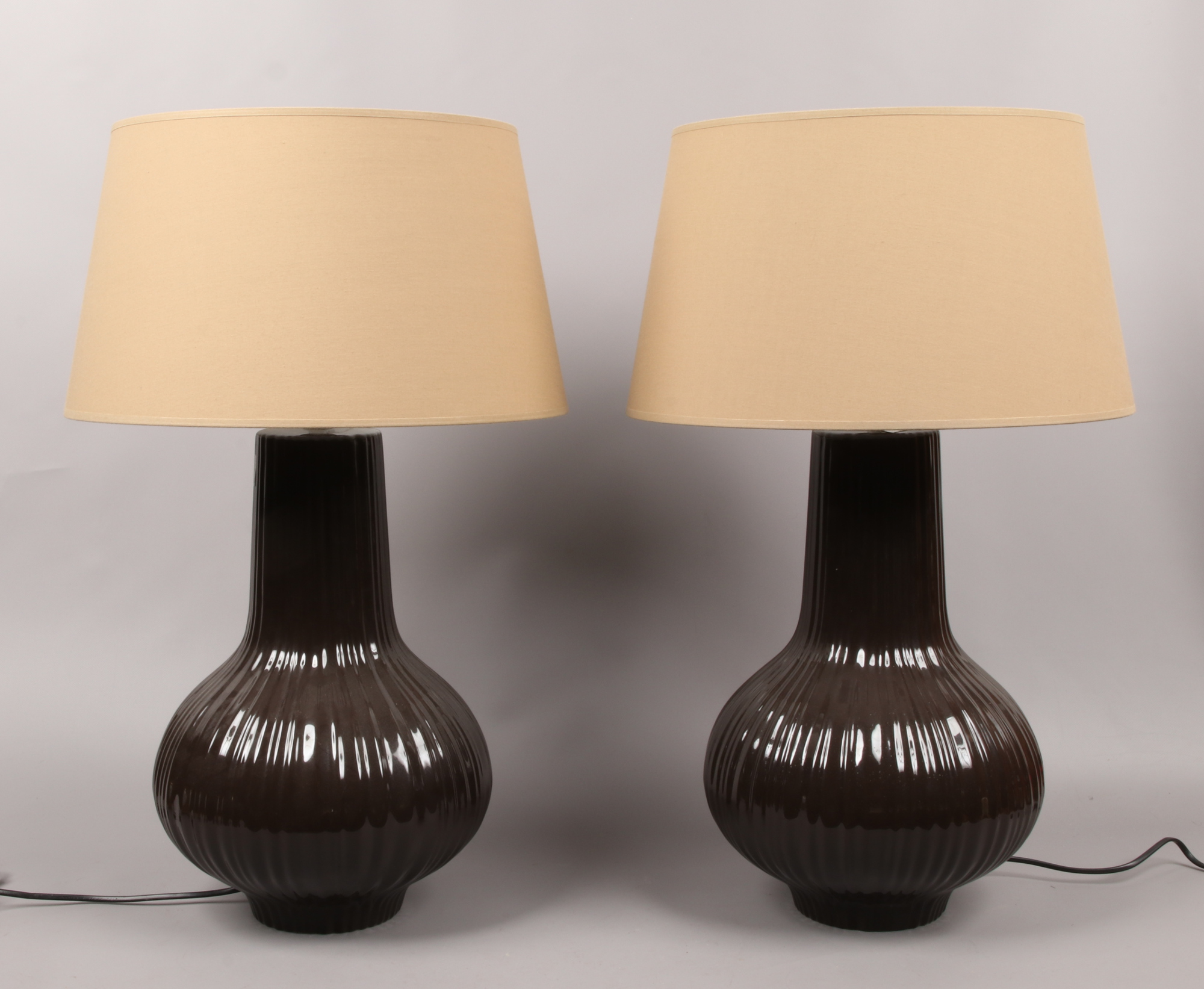Lot 21 - A pair of glazed pottery table lamps of baluster form with reeded decoration and coffee cream
