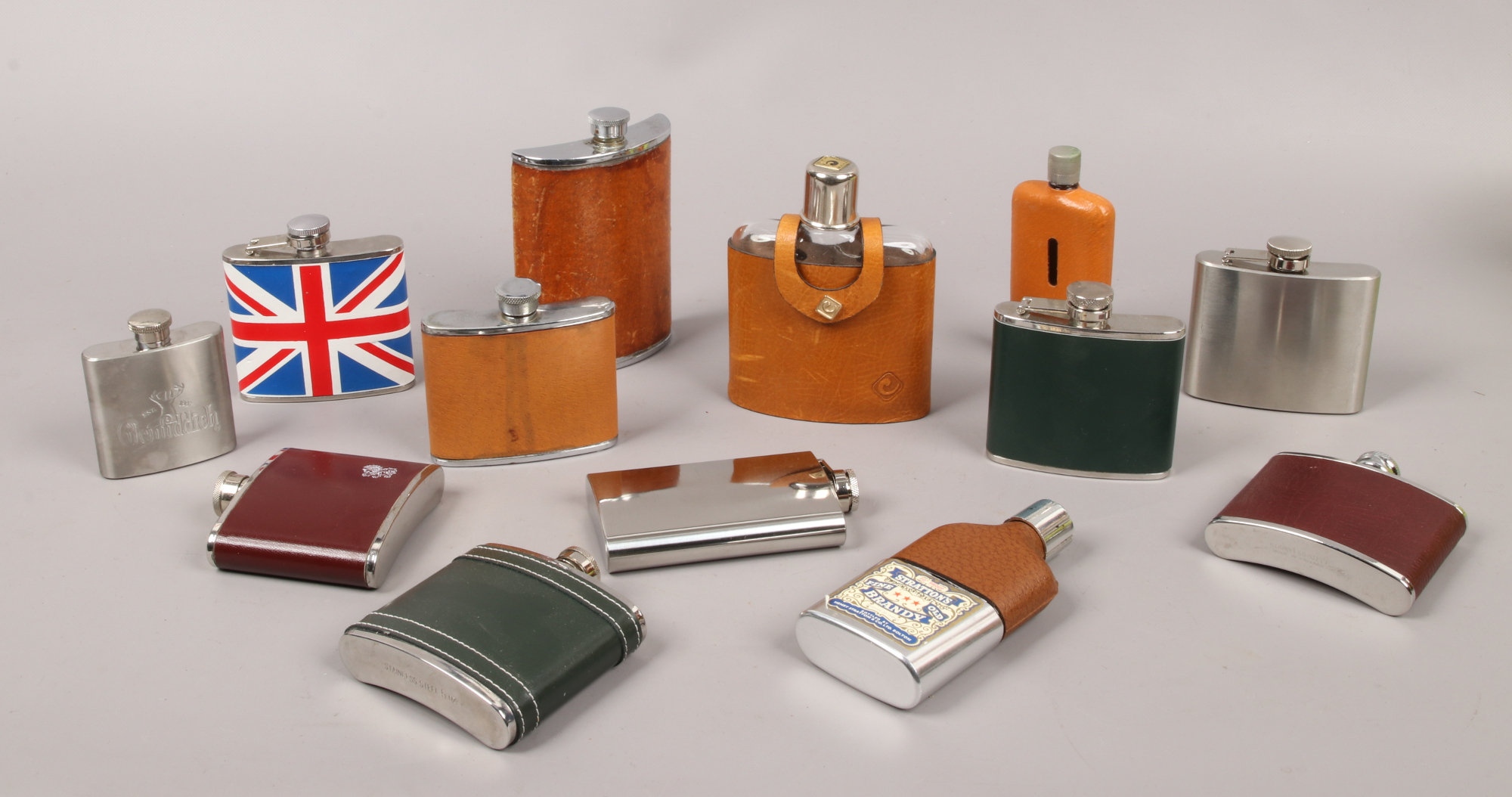 Lot 50 - A collection of hip flasks to include leather stainless steel examples etc.
