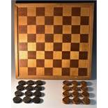 A 19th century boxwood and ebony treen draughts set, each piece engine turned with a sample design,