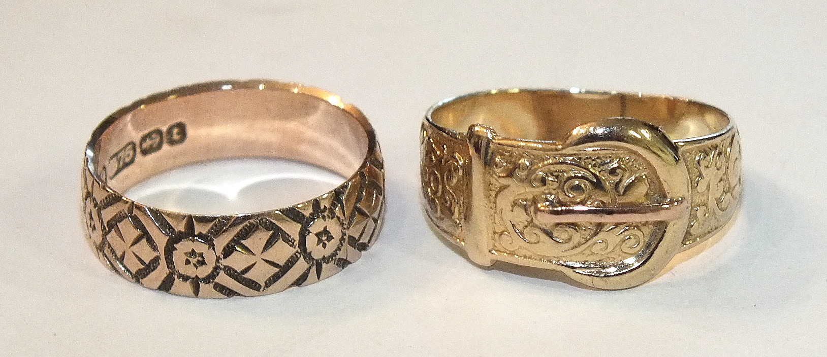 Lot 204 - A 9ct gold buckle ring, size Q, 3.2g and a 9ct gold wedding band, size O, 3.2g, (2).