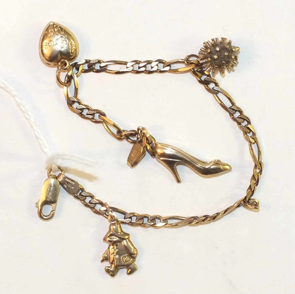 Lot 215 - A 9ct gold curb-link bracelet with four charms, 6.6g.