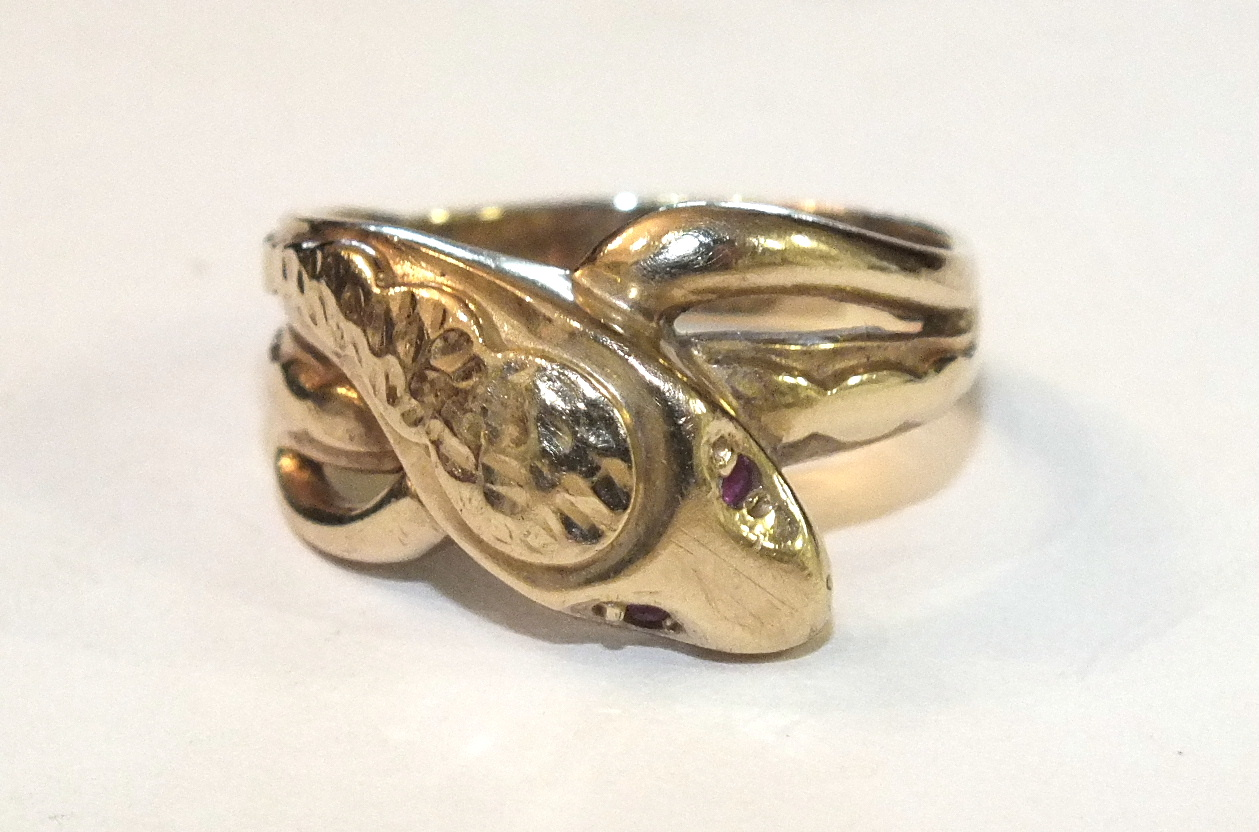 Lot 203 - A 9ct gold snake ring with red stone-set eyes, size R, 4.7g.