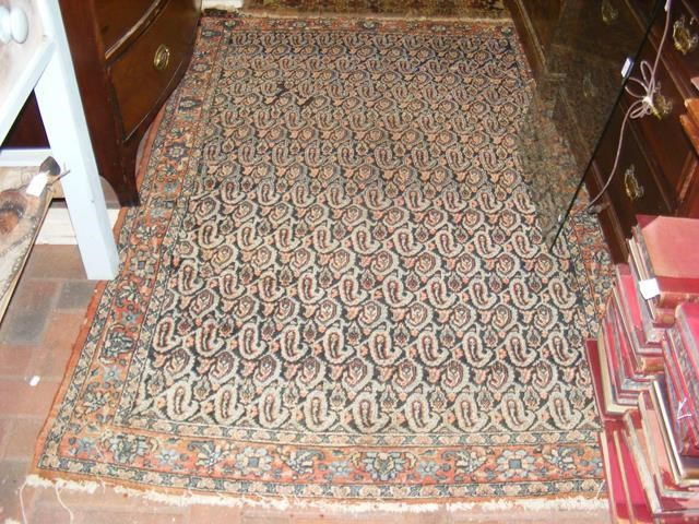 An antique Middle Eastern rug with geometric borde