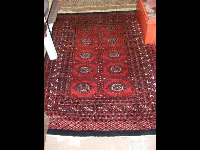 A Middle Eastern rug with geometric border and red