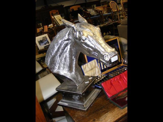 A silvered cast metal horse head on plinth - 54cm high
