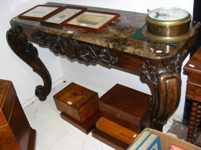 A decoratively carved console table with cabriole