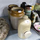 A STONEWARE HOT WATER BOTTLE AND TWO FAWN STONEWARE STORAGE JARS (3)