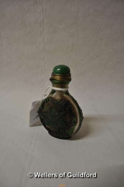 Lot 7415 - A Chinese glass snuff bottle, green cabochon stone to lid, carved with bats and leaves, 7cm.