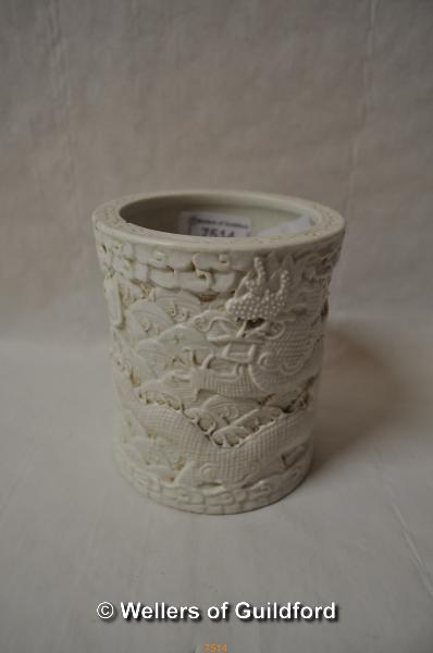 A Chinese cream porcelain brush pot decorated all over with dragons and dragon's scales, impressed