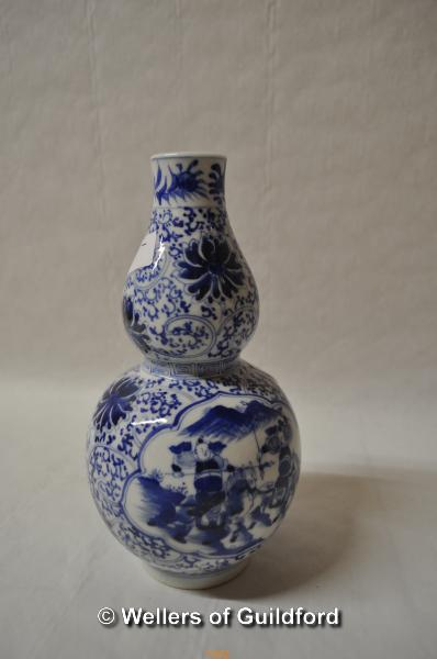 Lot 7442 - A Chinese blue and white double gourd vase decorated with warriors on horseback, 20cm.