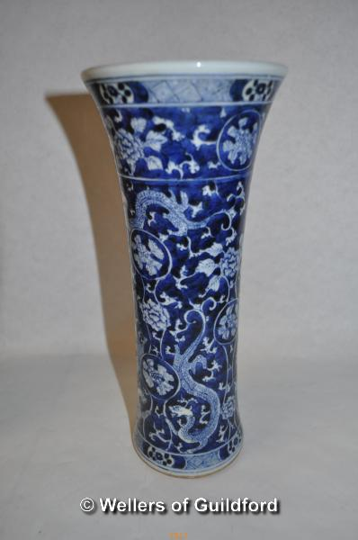 Lot 7517 - A Chinese blue and white sleeve vase with flared rim, decorated all over with dragons and foliage,