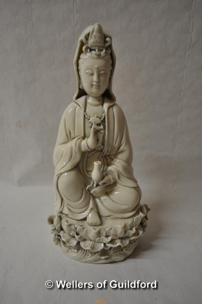 Lot 7513 - A Chinese blanc de chine figure of Guanyin seated on a lotus flower, 27cm.