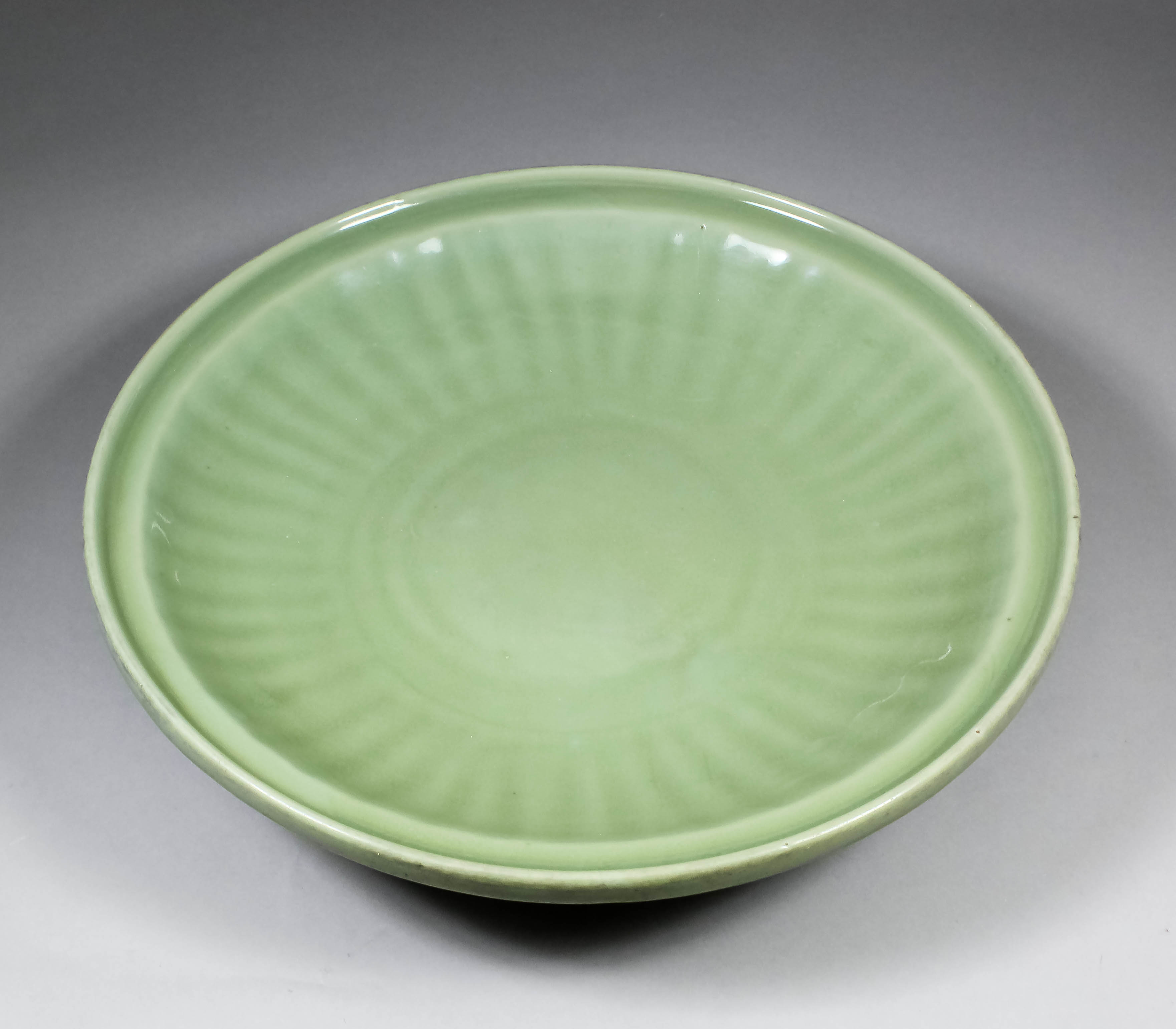 Lot 490 - A Chinese Longquan celadon glazed circular charger with fluted border and moulded rim, 15.75ins (