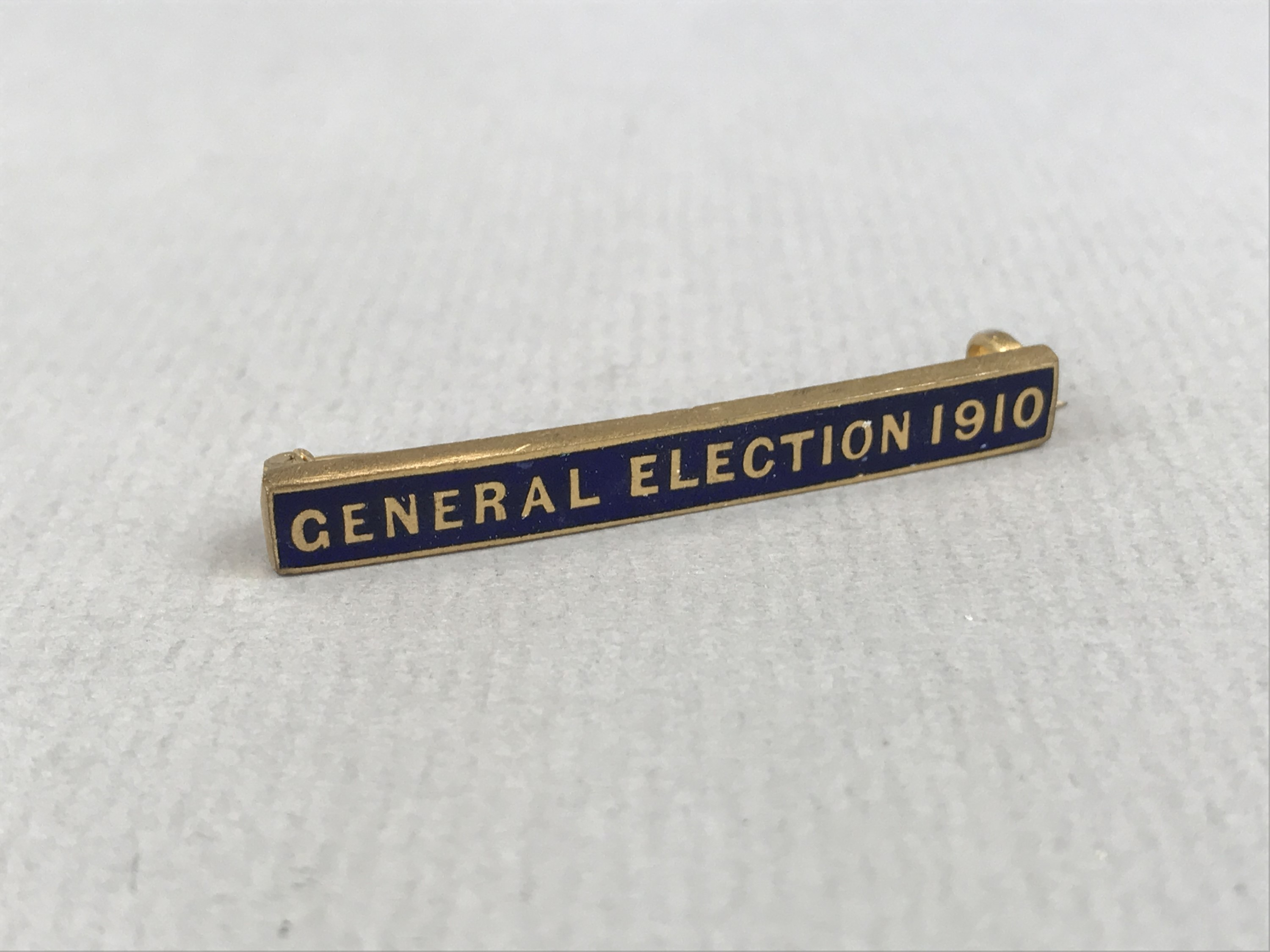 """Lot 40 - A """"General Election 1910"""" rolled-gold and enamelled bar brooch, manufactured by Wolewis of"""