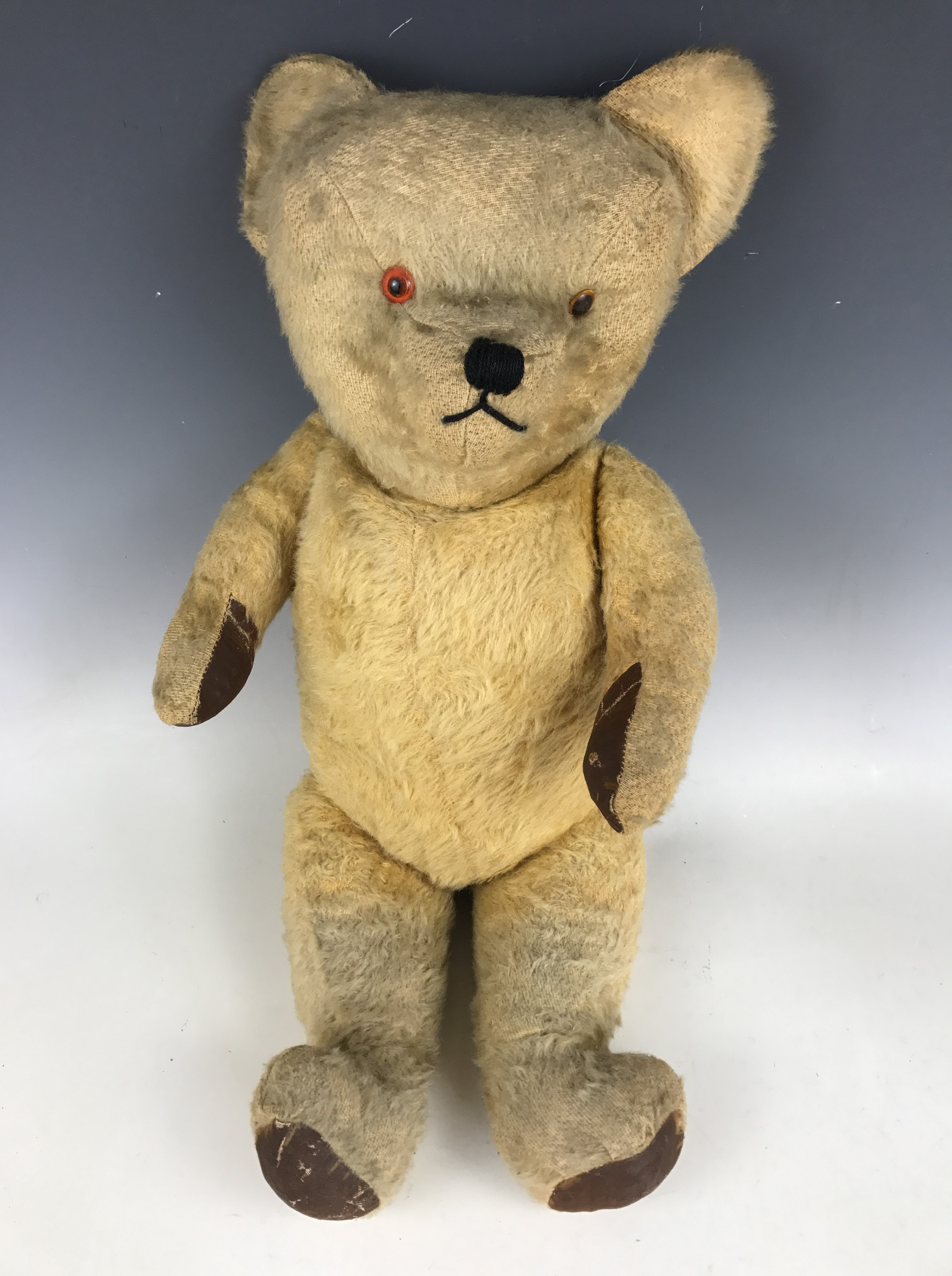 Lot 52 - A mid 20th Century growling Teddy bear, having blonde mohair, glass eyes and leather paw pads,