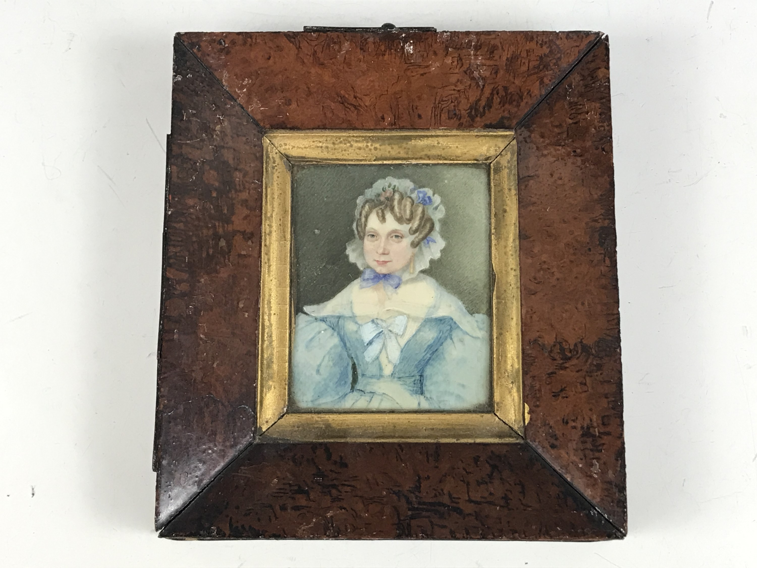 Lot 47 - A portrait miniature of a Georgian lady, wearing 1830s fashions, of a turquoise blue silk dress with