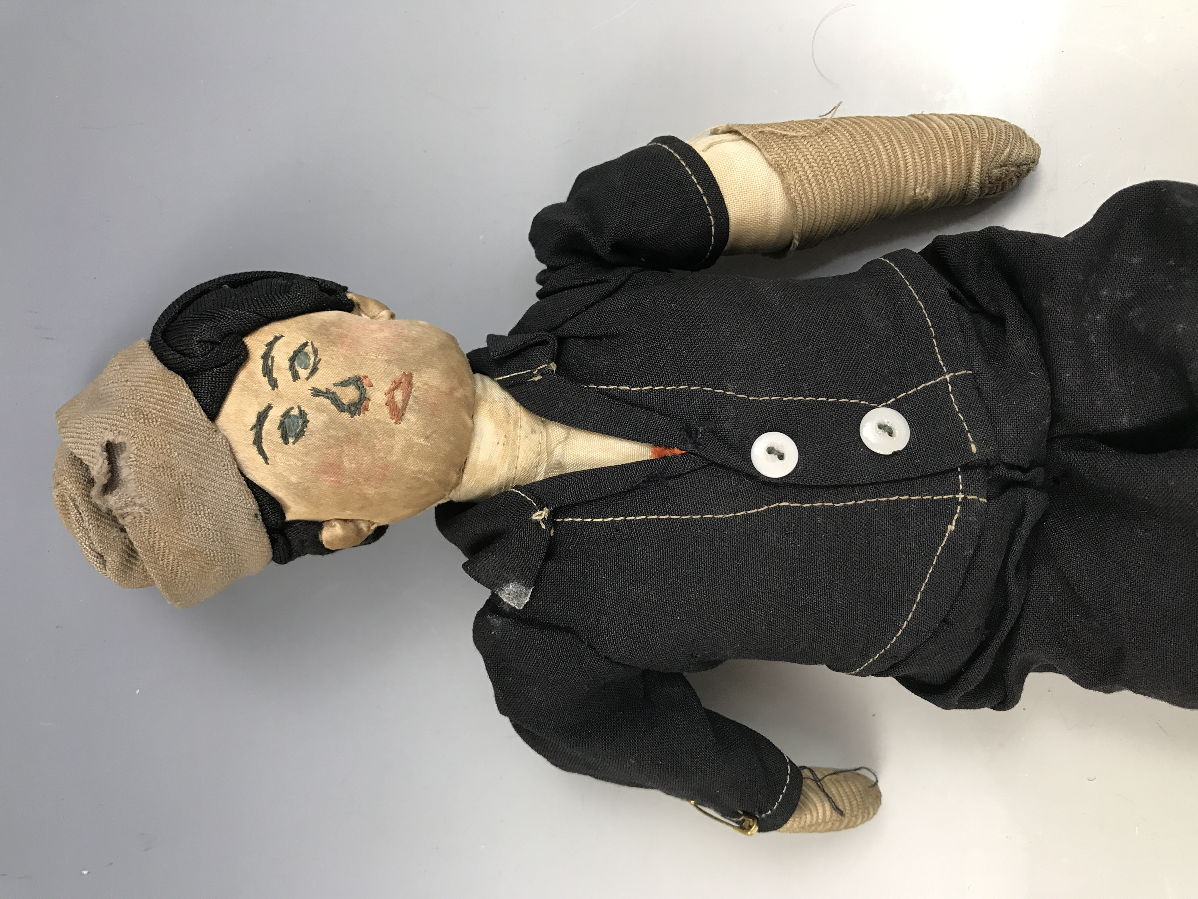 Lot 53 - A 1920s cloth doll, modelled as a young boy, wearing cloth cap, a black short suit and velvet boots,