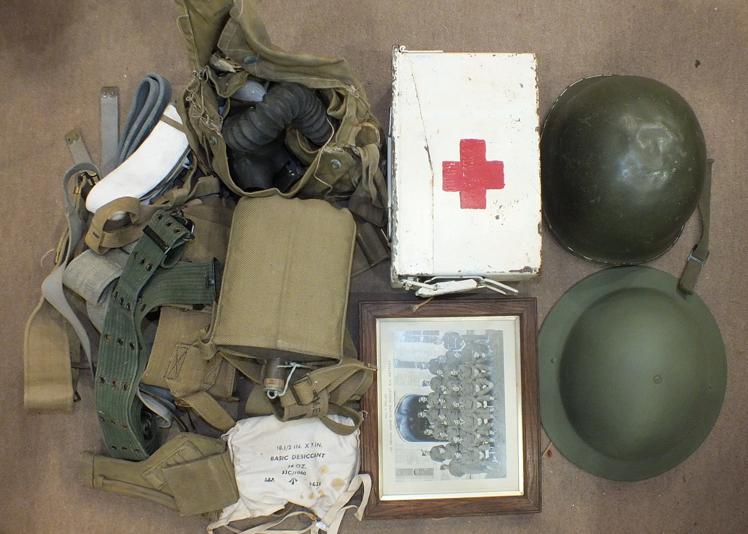 Lot 601 - A collection of WWII webbing, water bottle, tin helmet, American tin helmet and a photograph of