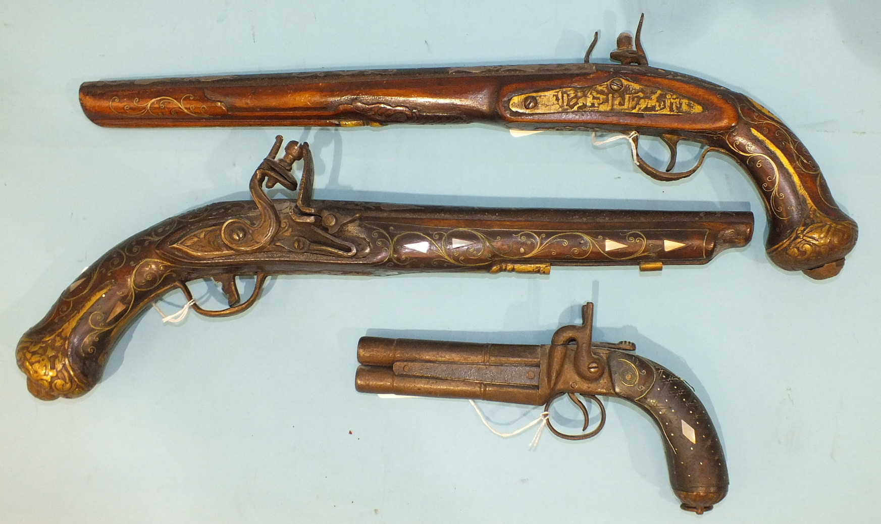 Lot 591 - A Continental double-barrelled percussion pistol with wire inlay walnut butt and iron fittings, over