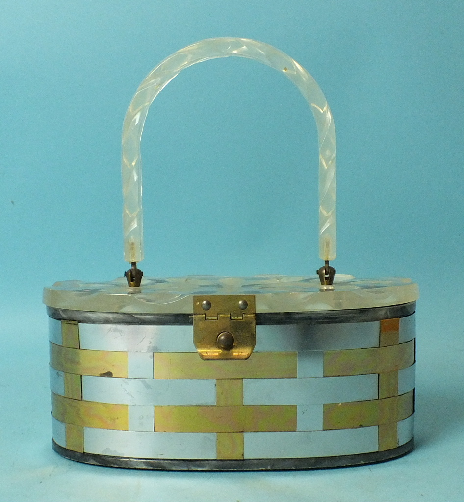 Lot 669 - A 1950's woven metal handbag of oval shape with incised clear Lucite lid and handle, 21cm long.