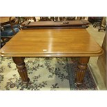 A late-19th century mahogany extending dining table on fluted legs with two extra small leaves and
