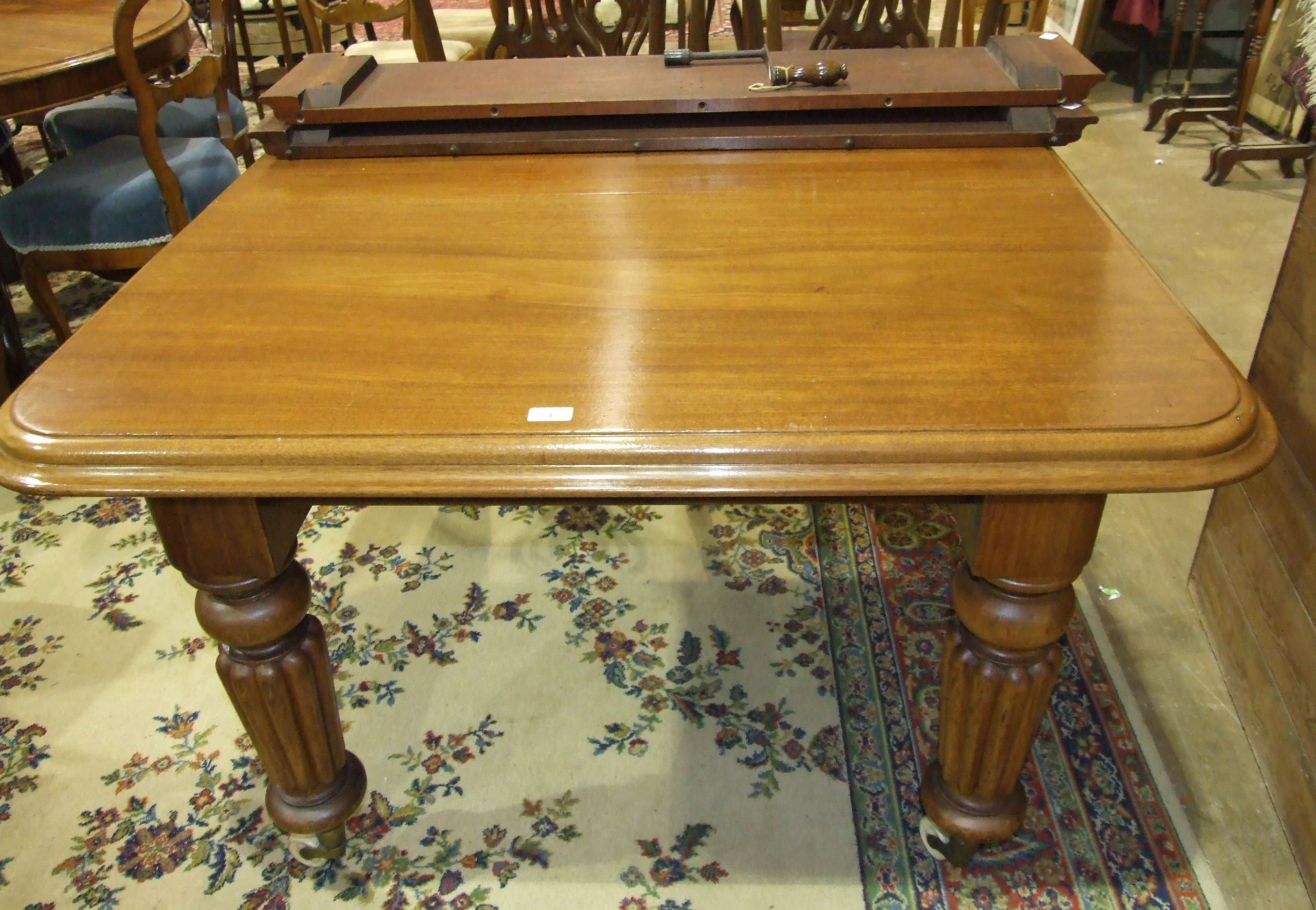 Lot 1 - A late-19th century mahogany extending dining table on fluted legs with two extra small leaves and