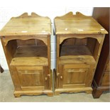 A pair of stained pine bedside cupboards, each fitted with a single door below a shelf, 41.5cm wide,