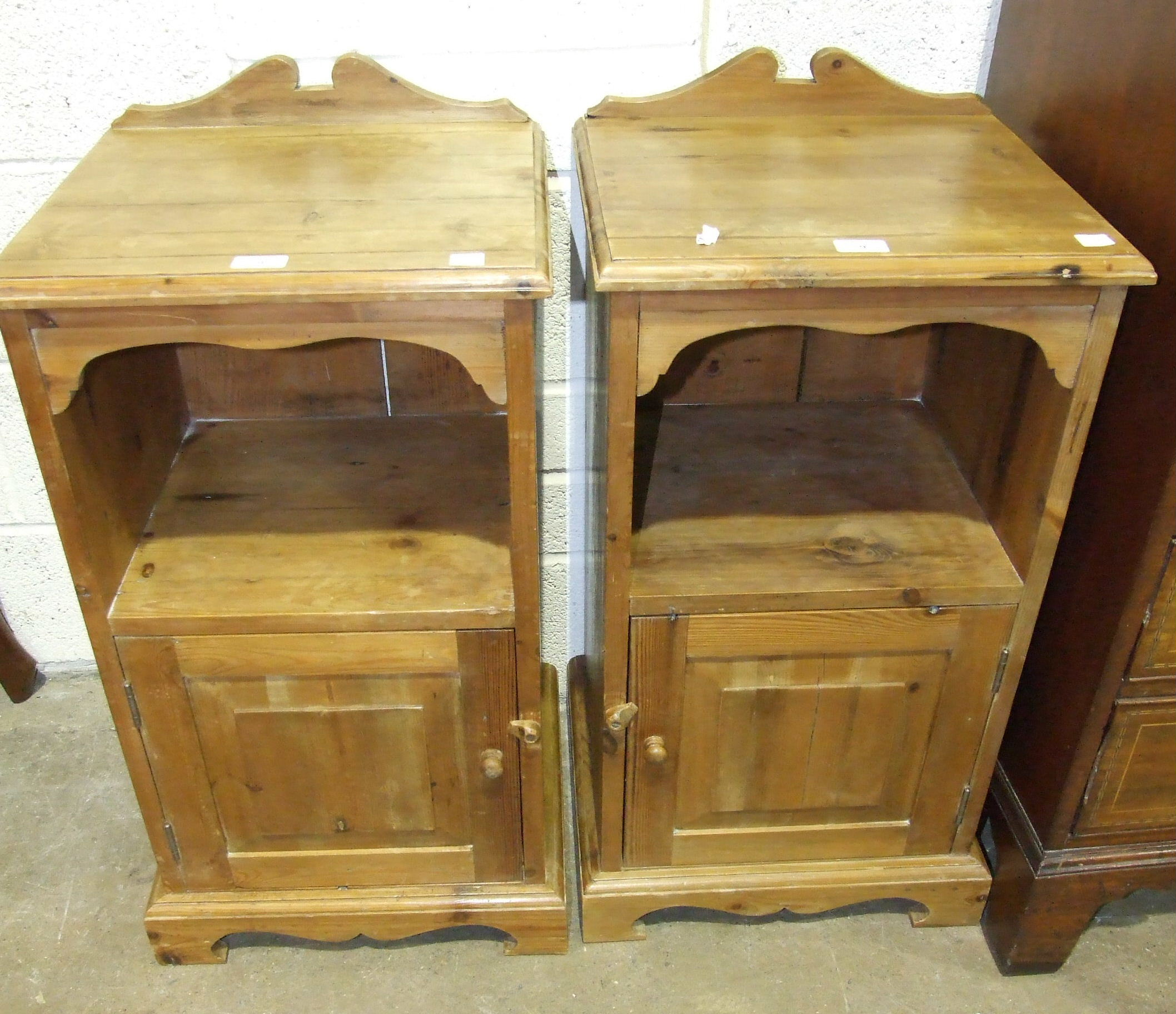 Lot 9 - A pair of stained pine bedside cupboards, each fitted with a single door below a shelf, 41.5cm wide,