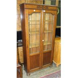 An oak bookcase fitted with a pair of leaded-light doors, 76cm wide, 159cm high.