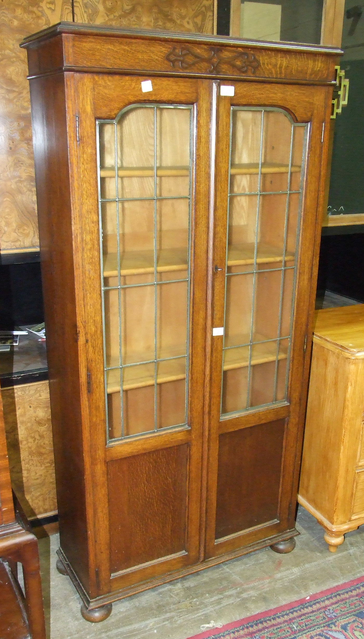 Lot 20 - An oak bookcase fitted with a pair of leaded-light doors, 76cm wide, 159cm high.