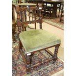 An upholstered-seat oak-framed nursing chair with carved spindle back and turned front legs.