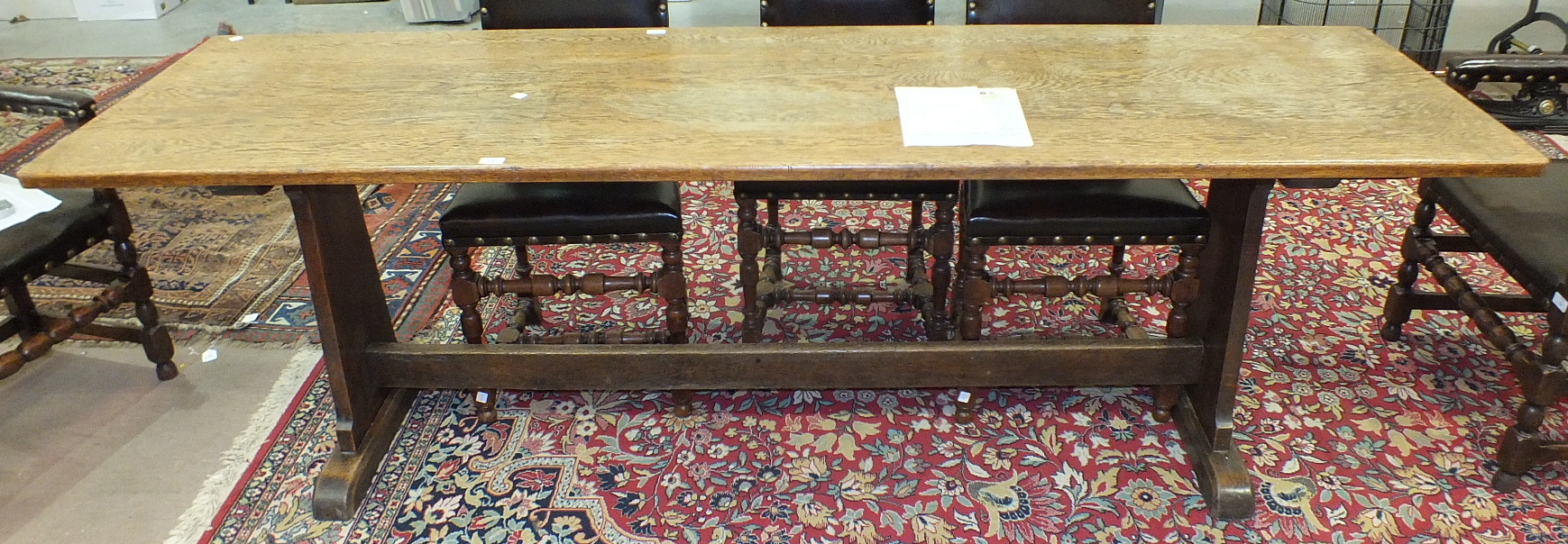 Lot 34 - An oak refectory-style narrow dining table, the rectangular top on tapered end supports united by