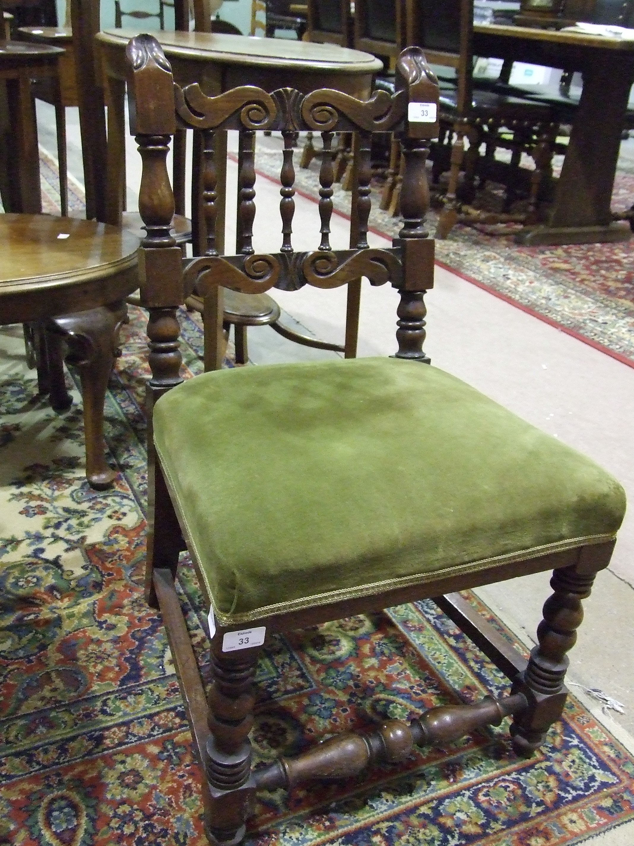 Lot 33 - An upholstered-seat oak-framed nursing chair with carved spindle back and turned front legs.
