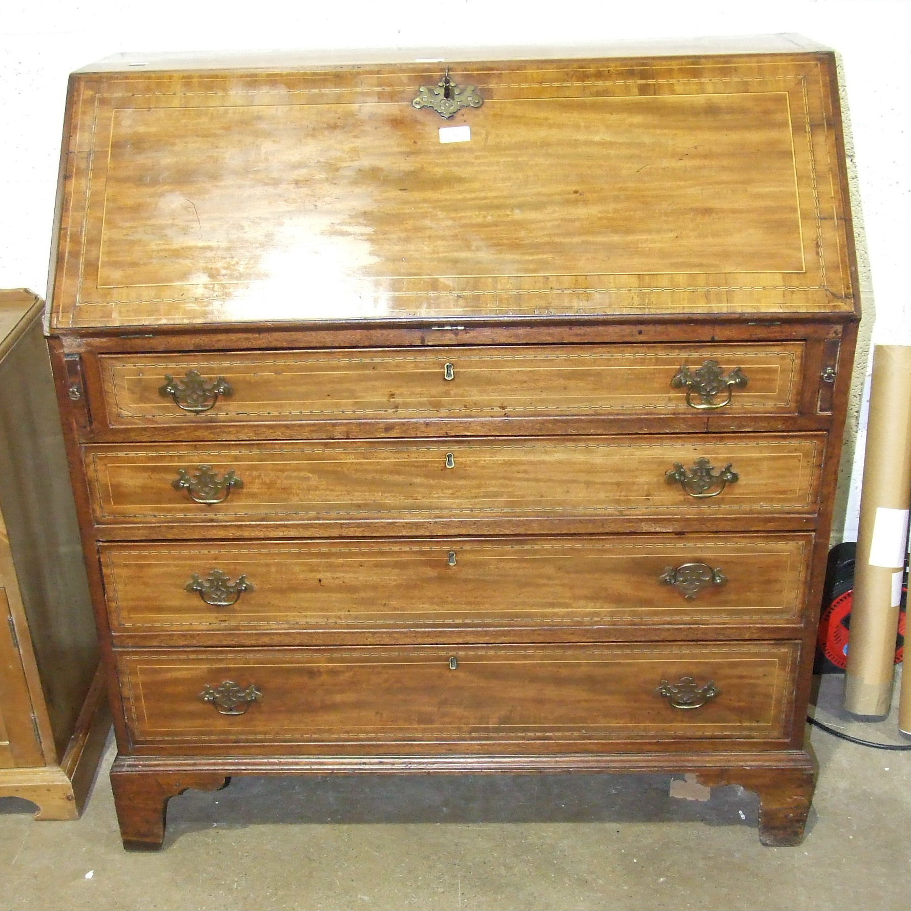 Lot 18 - A Georgian inlaid mahogany bureau, the fall front opening to reveal drawers and pigeon holes,
