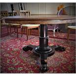 A 19th century mahogany circular dining table, raised on ebonised turned support on tri-form base