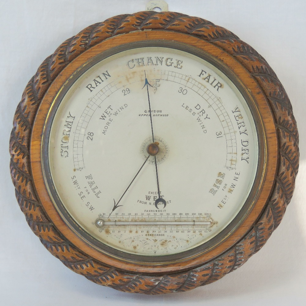 Lot 411 - A carved oak Victorian aneroid barometer