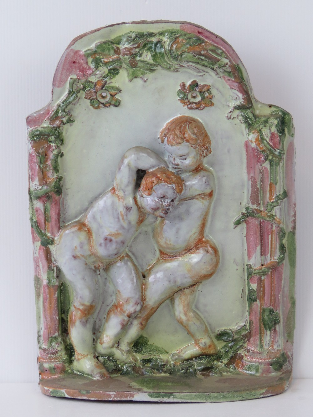A ceramic wall plaque featuring boys fig