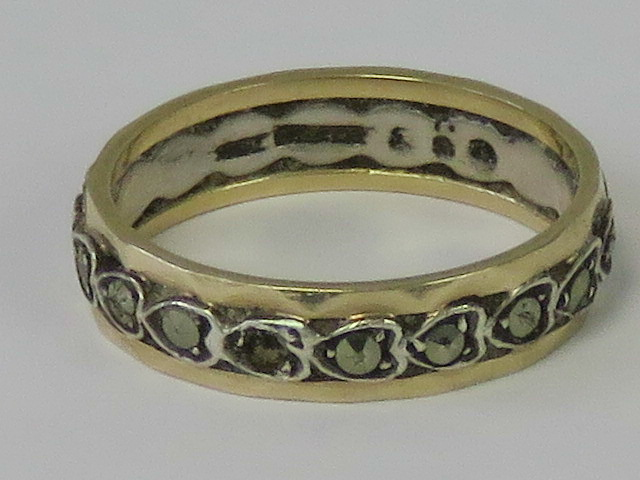 A silver and 9ct gold eternity ring, the