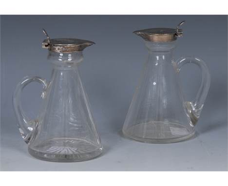 An Edwardian silver mounted clear glass conical whisky noggin, hinged cover with spoon-shaped thumb piece, scroll handle, sta