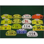Fifteen aluminium and plastic motoring rally plaques for the front of a vehicle from 1960-2004
