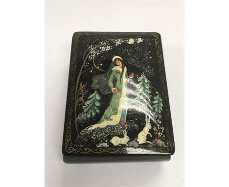 A Russian folk art papier mache box depicting a female figure ina winter landscape with rabbits at her feet, approx 5cm x. 6.