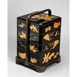 A BLACK LACQUER FOUR-TIER JUBAKO (CAKE BOX) AND COVER WITH A PORTABLE CASE Wood and lacquer.