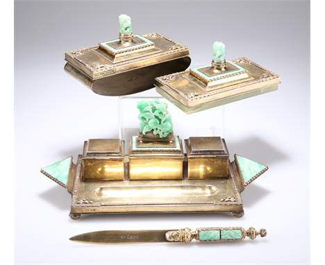 A FINE GEORGE V SILVER-GILT AND JADE DESK SET, by Charles Boyton, London 1935,comprising ink stand, with two clear-glas