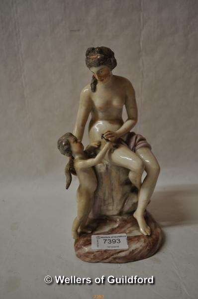 Lot 7393 - A 19th Century porcelain figure of a nude seated on a rock, a young cherub beside her, 21cm.