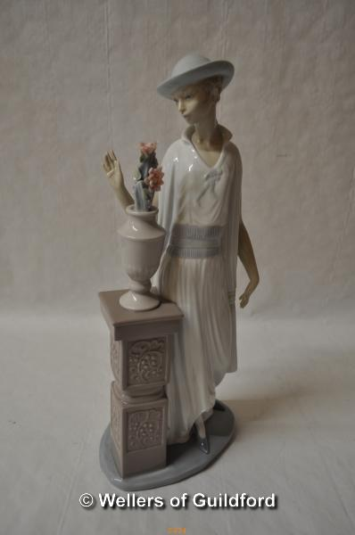 Lot 7474 - Lladro figure of a lady standing beside an urn of flowers, 35cm.