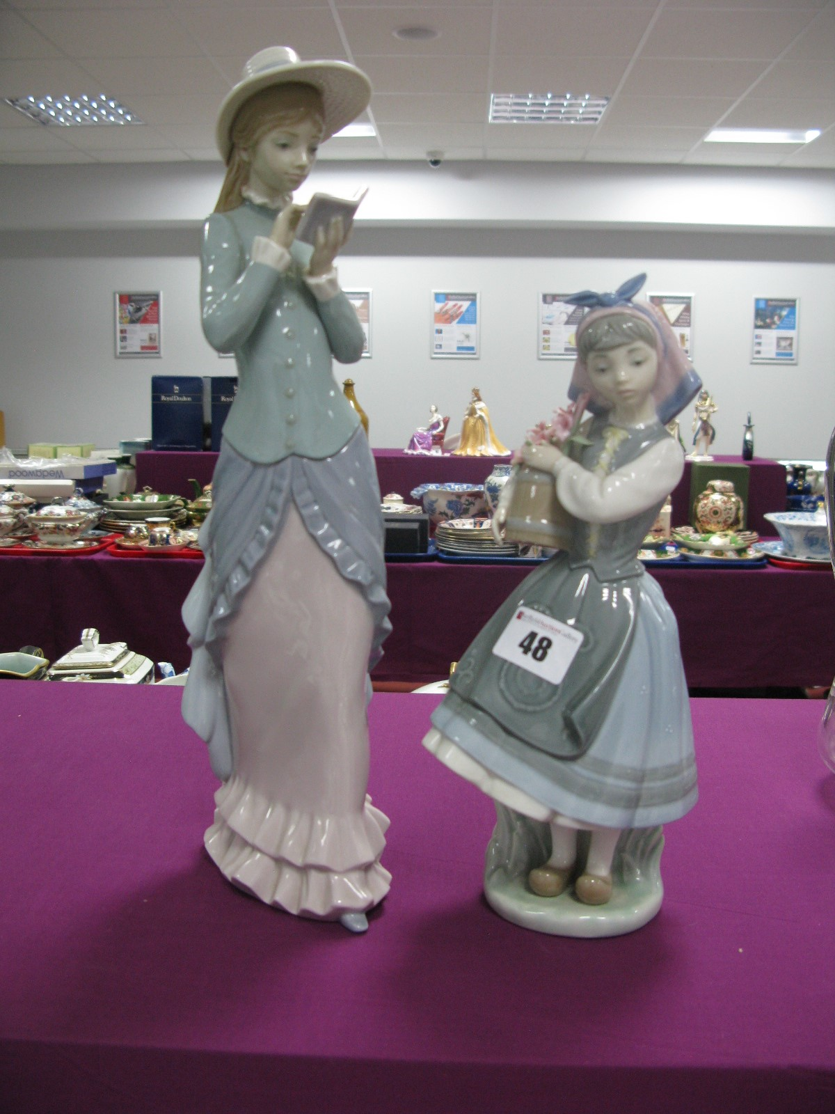 Two Lladro Models, 'lady walking whilst reading a book' and a 'young girl carrying a pail of